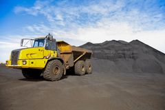Yellow Mining Dump Truck transporting Manganese for processing. Yellow Mining Dump Truck transporting Manganese ore rock for processing from the front Stock Photos
