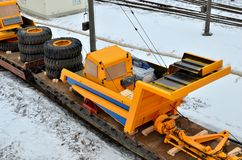 Yellow mining truck disassembled into parts, cab, body, electric motor, drive, wheels, loaded onto a cargo railway platform. Logistics of delivery of the truck stock photography