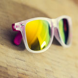 Yellow mirror plastic sunglasses on a wood background Stock Images