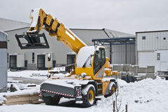 Yellow mobile crane. A snow-covered yellow mobile crane parked on a construction site Stock Images