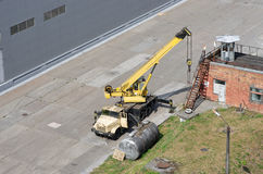 Yellow mobile crane in active state. With open cabin door beside canister and brick building Stock Photography