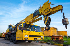 Yellow mobile crane. Against fuel oil storage tank area in power Stock Photography