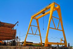Yellow mobile crane and ship under construction. Yellow mobile crane is working over dockyard Royalty Free Stock Photos