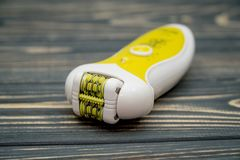 Yellow modern epilator on a wooden background. Removal of unwanted hair. Yellow modern epilator on a wooden background stock images