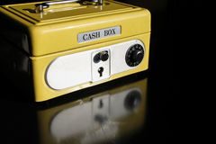 Yellow money box with numeric combination. Yellow cash box on black background, reflexes. security for your money with key lock and numeric combination stock image
