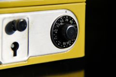 Yellow money box with numeric combination. Yellow cash box on black background, reflexes. security for your money with key lock and numeric combination Stock Photography