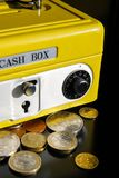 Yellow money box with numeric combination. Yellow cash box on black background, reflexes. security for your money with key lock and numeric combination and coins stock photography