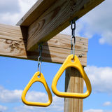 Yellow Monkey Bar Rings Against Blue Sky. Monkey bar rings on chains hanging from beam on playground Stock Images