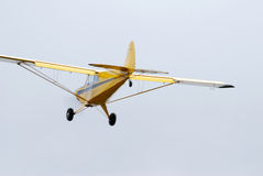 Yellow monomotor airplane low flight. Monomotor airplane makes a low pass shoot from rear Royalty Free Stock Photo