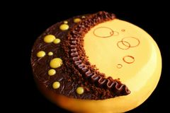 Yellow moon cake with chocolate ganache, pumpkin mousse and chocolate decoration stock image