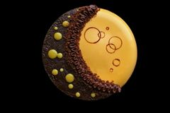 Yellow moon cake with chocolate ganache, pumpkin mousse and chocolate decoration top view stock image