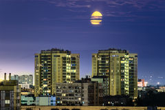 Yellow moon over sleeping district and buildings with illuminated windows Royalty Free Stock Photography
