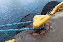 Yellow mooring bollard with blue naval rope Royalty Free Stock Photography