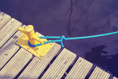 Yellow mooring bollard with blue rope. Vintage toned yellow mooring bollard with blue rope in marina, conceptual picture Stock Image