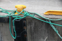 Yellow mooring bollard with green naval rope Stock Photography