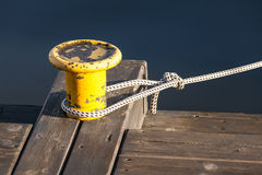 Yellow mooring bollard with nautical rope on pier Royalty Free Stock Image
