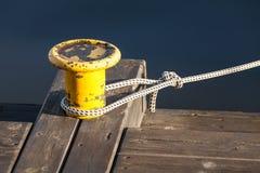 Yellow mooring bollard with nautical rope on pier Royalty Free Stock Image