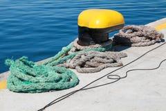 Yellow mooring bollard and nautical ropes Royalty Free Stock Photos