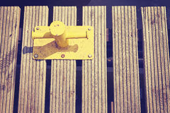 Yellow mooring bollard on wooden pier. Royalty Free Stock Image