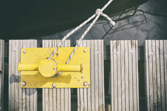 Yellow mooring bollard on wooden pier. Stock Images