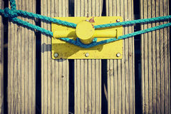 Yellow mooring bollard on wooden pier. Stock Image
