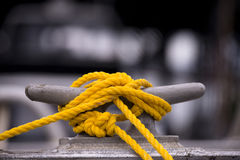 Yellow mooring rope on the hook. Yellow mooring rope node on the grey metall hook and blurred black and white background stock photo