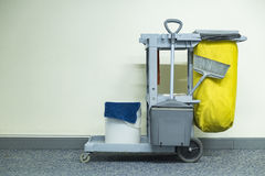 Yellow mop bucket and set of cleaning equipment Royalty Free Stock Photography