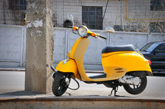 Yellow moped. Parked near the post Royalty Free Stock Photography