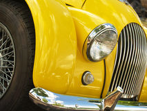 1966 Yellow Morgan Plus Four Front End. A uniquely-styled classic British car from the sixties in a bright lemon color. Partial view showing front end-- grille stock photography