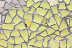 The yellow mosaics wall from the broken pieces of ceramicporcelain tiles. stock image