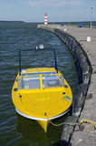 Yellow motor boat near sea dock and lighthouse Stock Image