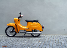 Yellow Motorbike by Grey Wall. A yellow motrobike parked by a grey concrete wall Royalty Free Stock Image