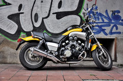 Yellow motorcycle. Parked in front of the building Stock Images