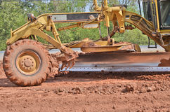 Yellow motorgrader on the road Stock Photos