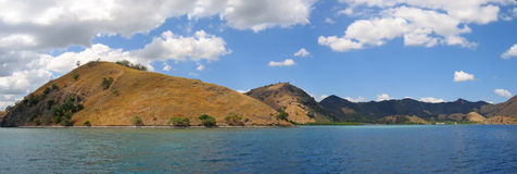 Yellow mountains. Falling on the sea - Komodo archipelago - Indonesia - Panorama Royalty Free Stock Photo