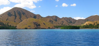 Yellow mountains on sea. Yellow mountains falling on the sea of Komodo archipelago - Indonesia - Panorama Stock Images