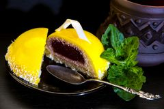 Yellow mousse cake on a black plate and a ceramic cup of coffee. Yellow mousse cake with glossy glaze and berry stuffing on a black saucer with a silver spoon Royalty Free Stock Image