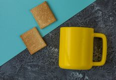 Yellow mug and cookies on dark stone table and blue paper with copy space stock image