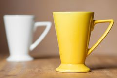 Yellow mug on the desktop. Yellow mug on the wooden table Royalty Free Stock Photography