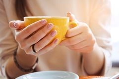 Yellow mug in the hands of a young woman. Girl holding a Cup of coffee in a cafe. Coffee break, Breakfast. The concept of power. stock photo