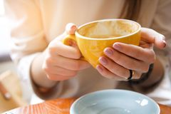 Yellow mug in the hands of a young woman. Girl holding a Cup of coffee in a cafe. Coffee break, Breakfast. The concept of power. stock image