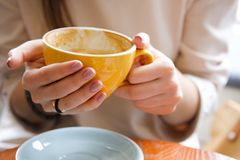 Yellow mug in the hands of a young woman. Girl holding a Cup of coffee in a cafe. Coffee break, Breakfast. The concept of power. royalty free stock photography