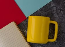 Yellow mug with notebook on dark stone background. Blue and red paper. With copy space royalty free stock image