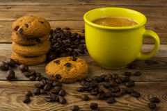Yellow mug of strong coffee and cookies royalty free stock image