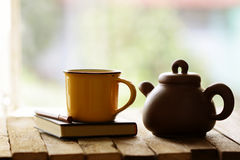 Yellow mug with vintage old teapot on wooden table Stock Image