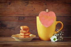 Yellow mug with a wooden vintage pink heart and cookies on the plate on wooden table Stock Images