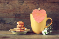 Yellow mug with a wooden vintage pink heart and cookies on the plate on wooden table Stock Image
