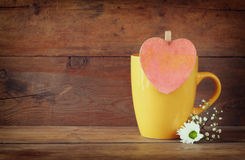 Yellow mug with a wooden vintage pink heart on wooden table Royalty Free Stock Image
