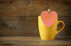 Yellow mug with a wooden vintage pink heart on wooden table Stock Images