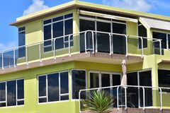Yellow multi-story holiday house. With verandas protected by glass railing and tinted glass windows Royalty Free Stock Images